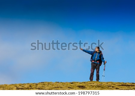 hiker in the mountains with deep blue sky and cope space