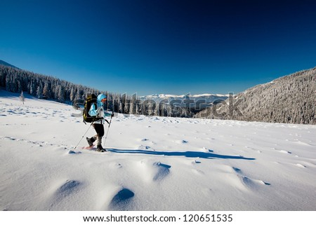 Hiker in winter mountains snowsheing