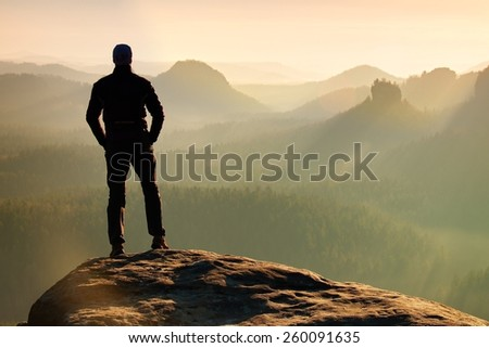 Hiker is standing on the peak of sandstone rock in rock empires park and watching over the misty and foggy morning valley to Sun. Beautiful moment the miracle of nature  - stock photo