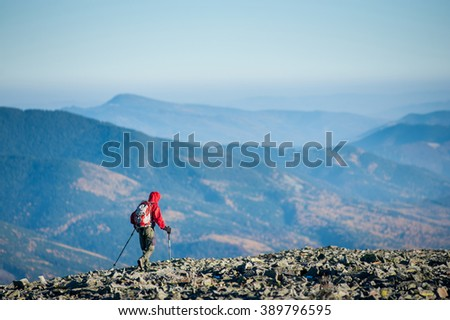 Hiker is walking on the rocky mountain plato on backpacking trip. Beautiful mountains on background. Rear view. Ecotourism and healthy lifestyle concept. Copy space. - stock photo