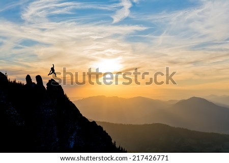 hiker jumps high in the air celebrating success in the sunset - stock photo