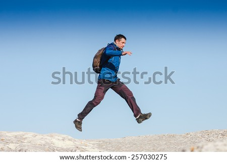 Hiker jumps on the rock - stock photo