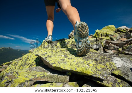 Hiker jumps over stones in Carpathian mountains with foot closeup - stock photo