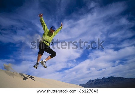 Hiker leaps from the summit of the Kelso Sand Dunes.