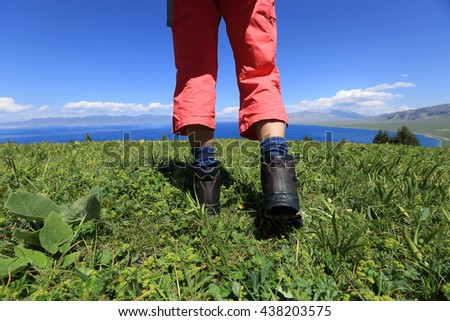 hiker legs on a grass mountain top with first person perspective view