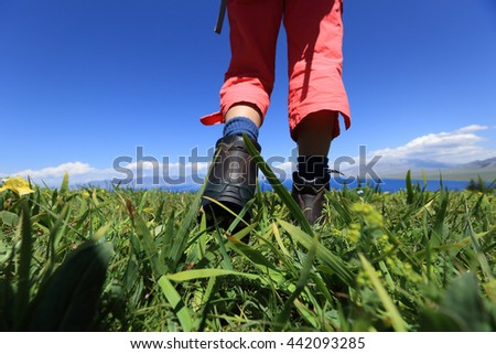 hiker legs on a grass mountain top with first person perspective view  - stock photo