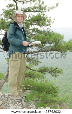 Hiker looking at a map while out trekking - stock photo