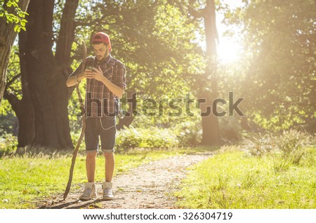 hiker looking at his smartphone during his tour in the forest - caucasian people - people, lifestyle, nature and technology concept - stock photo