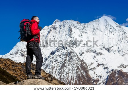 Hiker looking at the horizon in the mountains on sunny day - stock photo