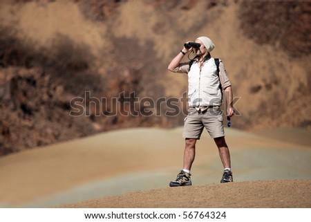 Hiker looking away through binoculars - stock photo