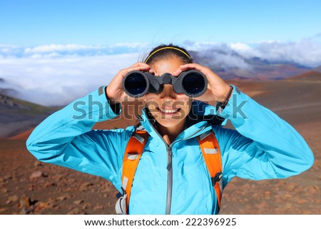 Hiker looking in binoculars enjoying spectacular view on mountain top above the clouds in Haleakala national park, Maui, Hawaii, USA. - stock photo