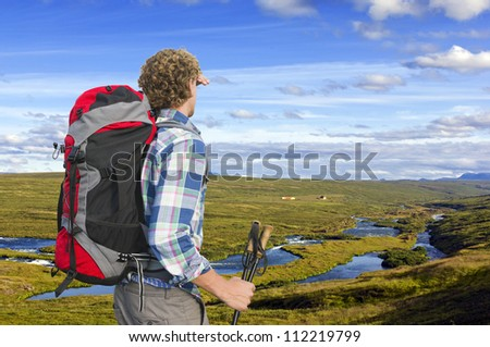 Hiker looking into the distance, upstream a small river, shielding his eyes and holding two walking sticks - stock photo