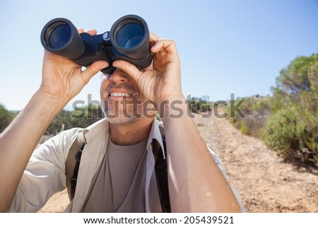 Hiker looking through his binoculars on country trail on a sunny day - stock photo