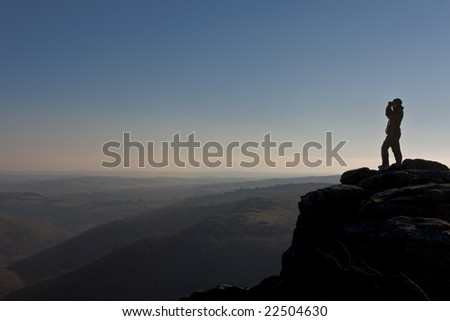 Hiker looks through binoculars over Dartmoor - stock photo