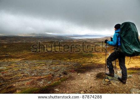 Hiker looks to the dark clouds - stock photo