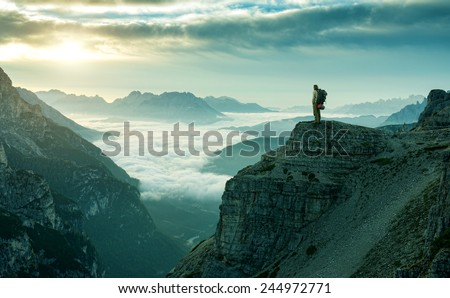 Hiker man at the rock cliff - stock photo