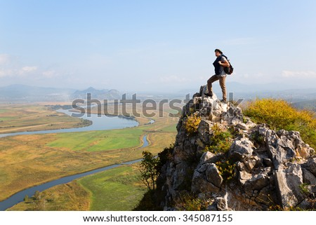 Hiker man climbed a mountain and admire nature. Autumn morning. - stock photo