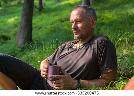 Hiker man is resting, lying on the green grass with cup of coffee, thinking about something. The mood for reflection.  Blurred green background. - stock photo