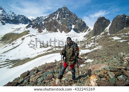 Hiker man on the summit with trekking poles. Snowy mountain landscape. Happy travel concept.