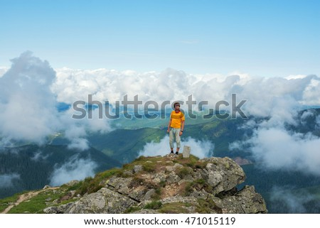 Hiker man stands on top among the clouds.  Wonderful evening in the mountains.