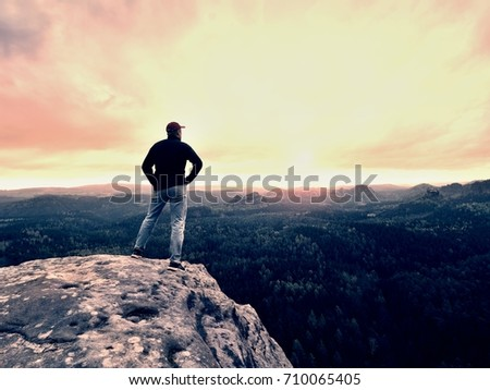 Hiker man stays on a rocky ridge and enjoy view over long valley to horizon. Cold Sun hidden in clouds. National park with a  rocky mountains and  valleys.