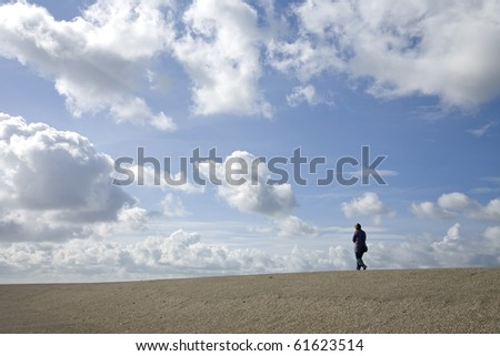 Hiker on a Dutch dike against a blue cloudy sky