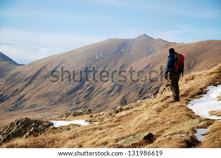 Hiker on a high mountain field, surround by peaks