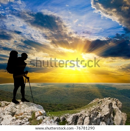 hiker on a mountain top at the sunset