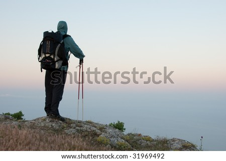 Hiker on a peak enjoys sea landscape - stock photo