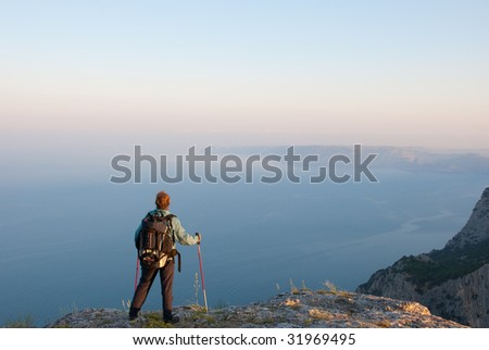 Hiker on a peak enjoys seashore landscape - stock photo
