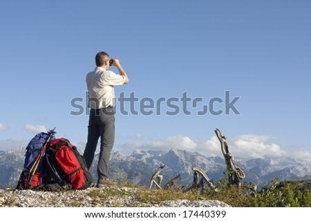 Hiker on mountain summit looking through field glasses - stock photo
