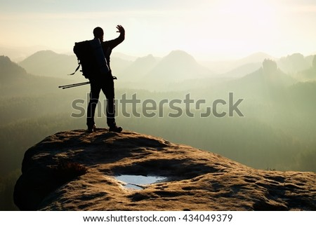 Hiker on peak. Backpacker with poles in hand shadowing eyes. Sunny spring daybreak in rocky mountains. Hiker on rocky view point above misty valley.  - stock photo