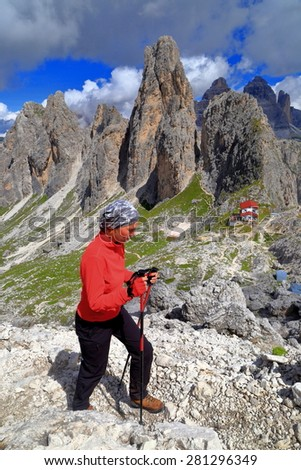 Hiker on sunny trail ascending from Savio Fonda refuge, Cadini di Misurina, Dolomite Alps, Italy - stock photo