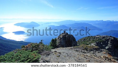 Hiker on the ridge of Mount Brunswick in Cypress Provincial Park near Vancouver, British Columbia, Canada. The spectacular Howe Sound, North America southernmost fjord in the background. - stock photo