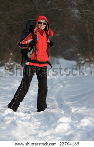 Hiker on the snow in winter forest
