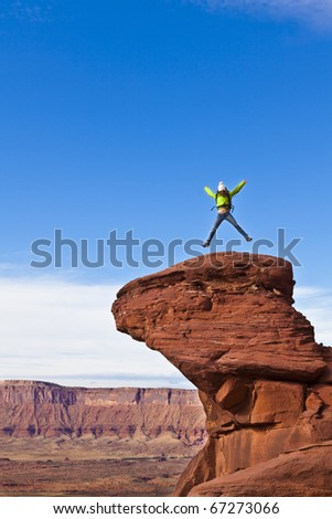 Hiker on the summit of a sandstone spire in Canyonlands National Park.