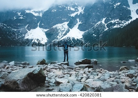 Hiker on the top enjoys mountain landscape