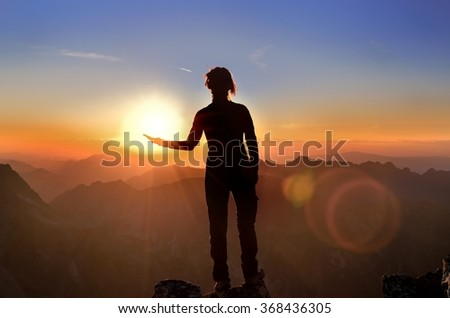 Hiker on the top holding in his hand the sun. Woman in the High Tatra Mountains at sunset.