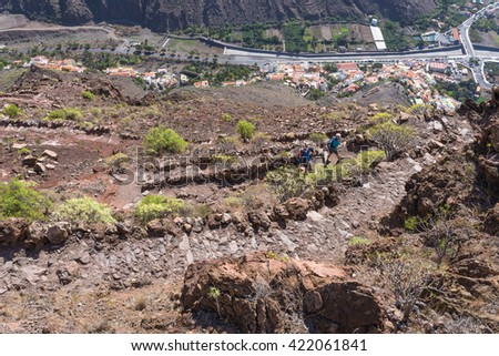 Hiker on the trail from the Valle Gran Rey to the village Arure in the highlands of the Canary island on La Gomera. 850m up on serpentine to the La Merica plateau on top of the mountain - stock photo