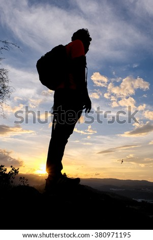 Hiker on top of the mountain enjoying sunrise.