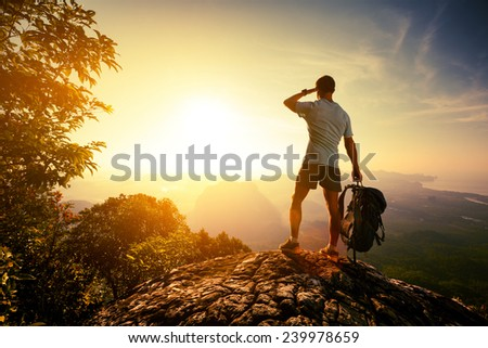 Hiker on top of the mountain enjoying sunrise over the tropical valley - stock photo