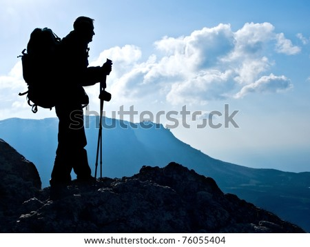 Hiker on top, silhouetted in high mountains - stock photo