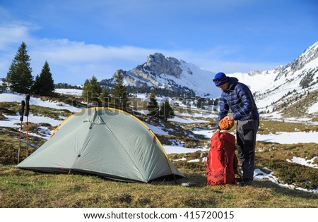 Hiker packing his backpack after camping in the mountains during springtime.