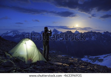 Hiker photographing the moon rising above the famous Matterhorn mountain in Switzerland. Outdoor and adventure concept.
