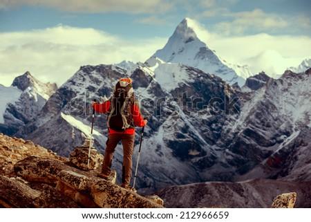 Hiker posing at camera on the trek in Himalayas, Nepal - stock photo
