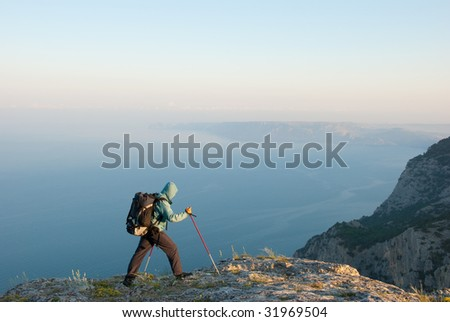 Hiker reaches peak with beautiful view to seashore landscape - stock photo