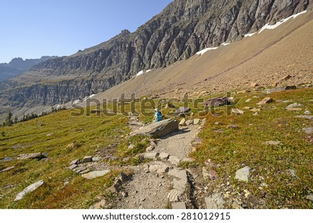 Hiker Relaxing on a Mountain Trail near Hidden Lake in Glacier National Park in Montana - stock photo