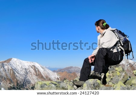 Hiker relaxing on rocky hill with clear blue sky