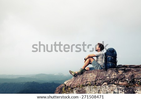 Hiker relaxing on top of the mountain - stock photo