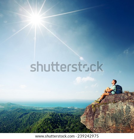 Hiker relaxing on top of the mountain at sunny day - stock photo